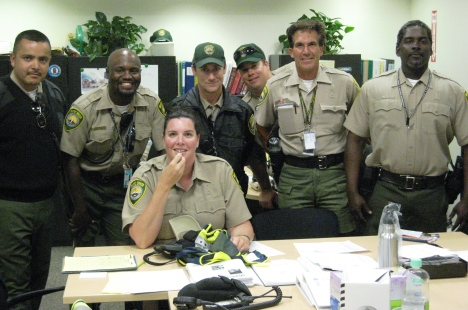 Airport Authority Vice President of Planning & Operations Angela tests a whistle surrounded by Airport Traffic Officers (back row from left) Jesus, Tieri, Alan, Jake and Vito.